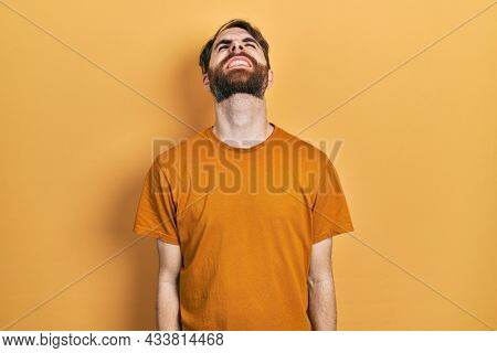 Caucasian man with beard wearing casual yellow t shirt angry and mad screaming frustrated and furious, shouting with anger. rage and aggressive concept.