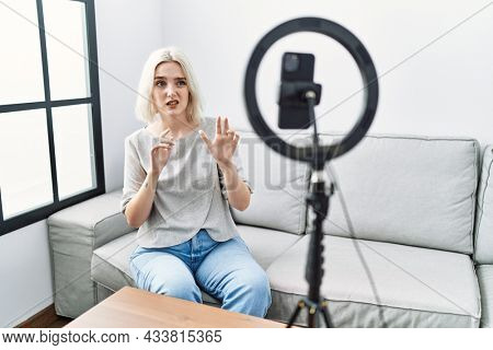 Young caucasian woman recording vlog tutorial with smartphone at home disgusted expression, displeased and fearful doing disgust face because aversion reaction. with hands raised