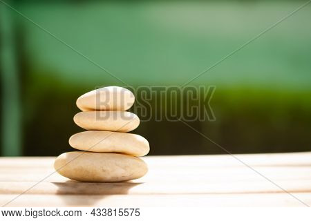 Stack Pyramid Stone Zen Pebbles On Wooden With Dark Black And Green Blur Background.free Space For A