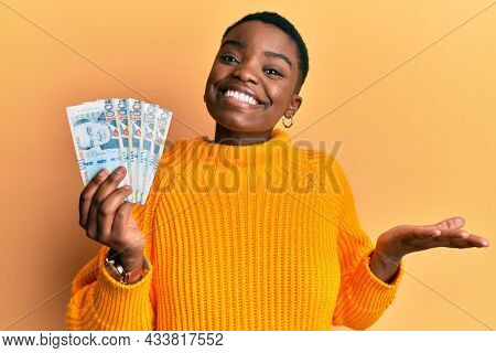 Young african american woman holding peruvian sol banknotes celebrating achievement with happy smile and winner expression with raised hand