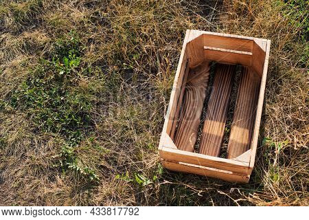 High Angle View At Empty Wood Plank Crate On Dry Grass Summer Time