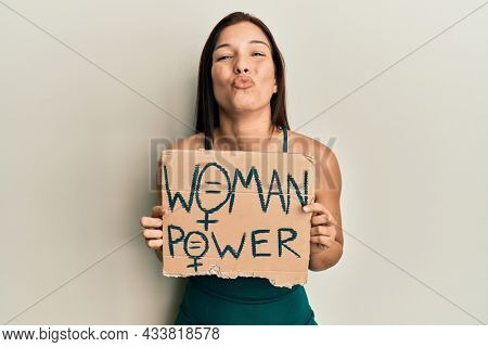 Young latin woman holding woman power banner looking at the camera blowing a kiss being lovely and sexy. love expression.