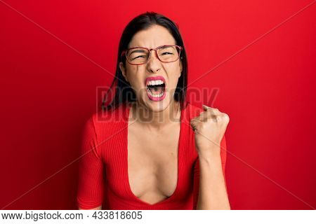 Young latin woman wearing casual clothes and glasses angry and mad raising fist frustrated and furious while shouting with anger. rage and aggressive concept.