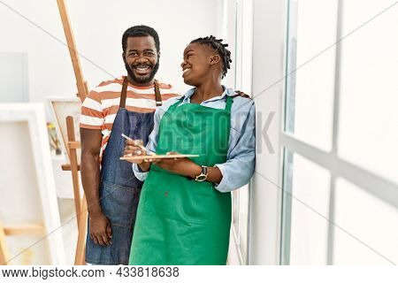 African american painter couple smiling happy holding paintbrush and palette leaning on the wall at art studio.