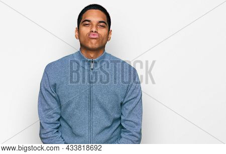 Young handsome hispanic man wearing casual sweatshirt looking at the camera blowing a kiss on air being lovely and sexy. love expression.