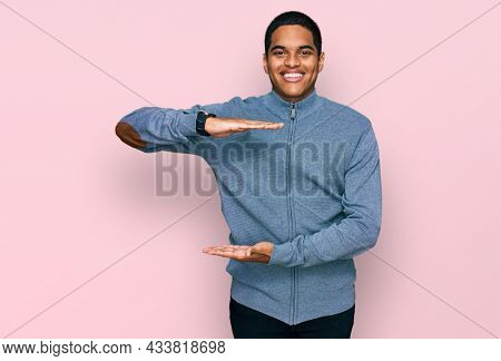 Young handsome hispanic man wearing casual sweatshirt gesturing with hands showing big and large size sign, measure symbol. smiling looking at the camera. measuring concept.