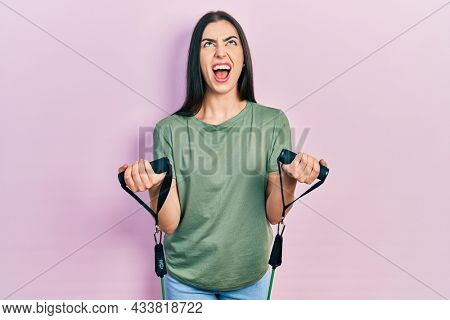 Beautiful woman with blue eyes training arm resistance with elastic arm bands angry and mad screaming frustrated and furious, shouting with anger looking up.