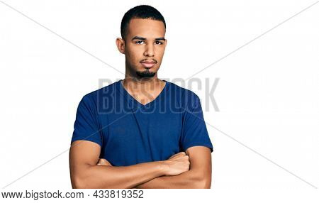 Young african american man with arms crossed gesture relaxed with serious expression on face. simple and natural looking at the camera.