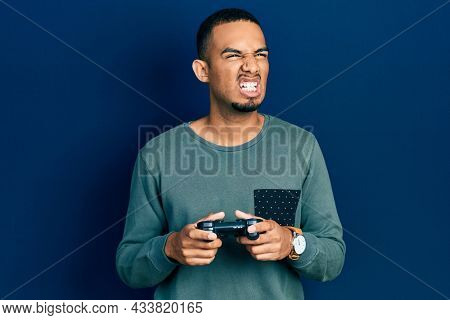 Young african american man playing video game holding controller angry and mad screaming frustrated and furious, shouting with anger. rage and aggressive concept.