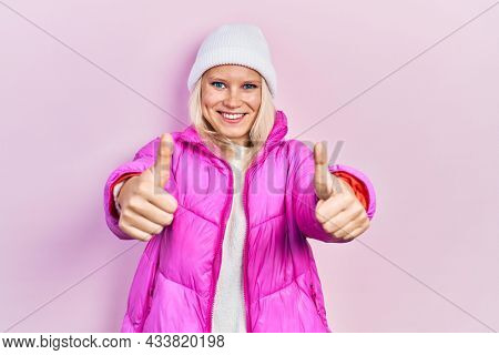 Beautiful caucasian blonde woman wearing wool hat and winter coat approving doing positive gesture with hand, thumbs up smiling and happy for success. winner gesture.