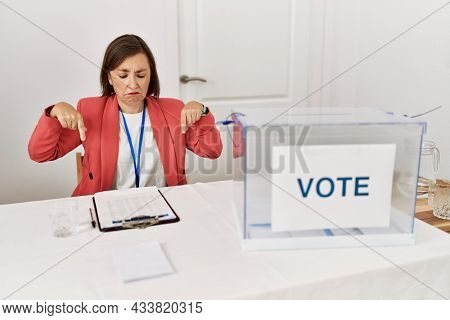 Beautiful middle age hispanic woman at political election sitting by ballot pointing down looking sad and upset, indicating direction with fingers, unhappy and depressed.