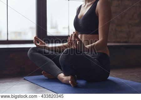 Cropped image of sportswoman sitting in lotus pose and practicing yoga. Concept of healthy lifestyle. Girl wearing sportswear meditating with closed eyes. Room with brick wall and wooden floor