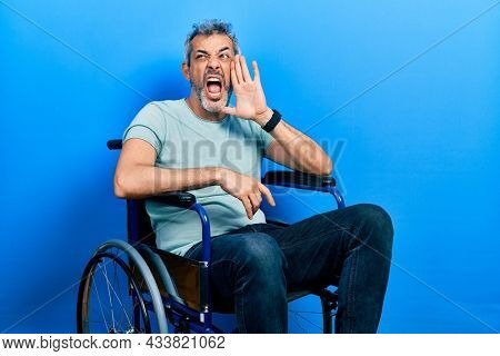 Handsome middle age man with grey hair sitting on wheelchair shouting and screaming loud to side with hand on mouth. communication concept.