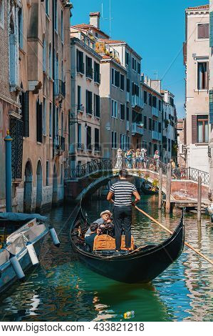 Venice, Italy-august 2021: The Venetian Canal With A Gondola Taking Tourists Along The Canals. Beaut