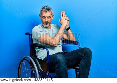 Handsome middle age man with grey hair sitting on wheelchair holding symbolic gun with hand gesture, playing killing shooting weapons, angry face