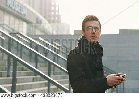 Young focused european businessman standing with mobile phone in city. Concept of modern successful man. Handsome stylish guy wearing scarf, coat and glasses. Sunny daytime