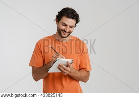Young brunette man with bristle smiling while writing down notes isolated over white background