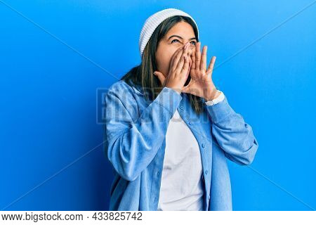 Young latin woman wearing cute wool cap shouting angry out loud with hands over mouth