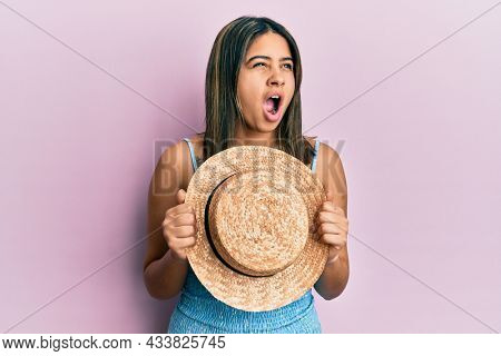 Young latin woman holding summer hat angry and mad screaming frustrated and furious, shouting with anger. rage and aggressive concept.