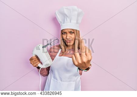 Beautiful hispanic woman holding pastry blender electric mixer showing middle finger, impolite and rude fuck off expression