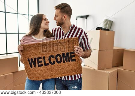 Young caucasian couple smiling happy holding welcome doormat at new home.