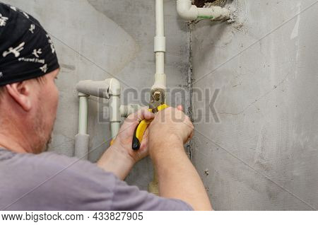 The Locksmith Is Repairing A Pipeline. Adult Male Pliers Unscrew The Coarse Water Filter. Inside The