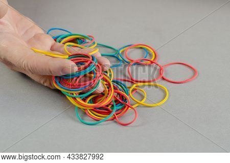 One Mans Hand Holds The Rubber Bands. Group Of Multi-colored Round Rubber Bands On A Gray Background