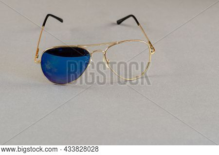 Sunglasses With One Glass On Gray Background. Yellow Metal Frame Of Sunglasses With Broken Glass. Cl