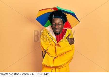 Young african american man wearing yellow raincoat hugging oneself happy and positive, smiling confident. self love and self care