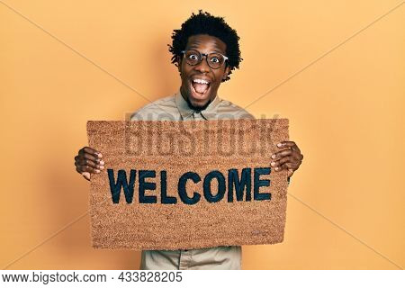 Young african american man holding welcome doormat celebrating crazy and amazed for success with open eyes screaming excited.