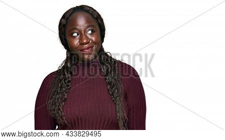 Young african woman wearing casual winter sweater smiling looking to the side and staring away thinking.