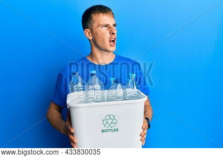 Young caucasian man holding recycling wastebasket with plastic bottles angry and mad screaming frustrated and furious, shouting with anger. rage and aggressive concept.