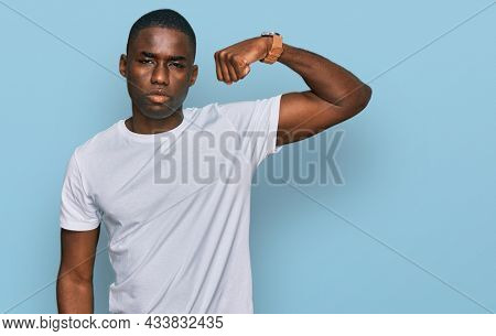 Young african american man wearing casual white t shirt strong person showing arm muscle, confident and proud of power