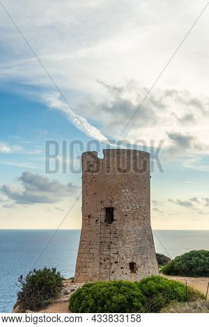 Ancient Watchtower Of Cap Blanc Made Of Stone On The Rocky Coast Of The Island Of Mallorca. In The B
