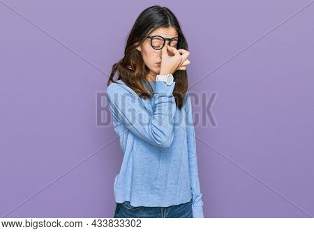Young beautiful woman wearing casual clothes and glasses tired rubbing nose and eyes feeling fatigue and headache. stress and frustration concept.