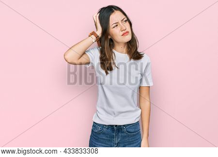 Young beautiful woman wearing casual white t shirt confuse and wondering about question. uncertain with doubt, thinking with hand on head. pensive concept.
