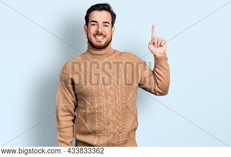 Young hispanic man wearing casual clothes showing and pointing up with finger number one while smiling confident and happy.