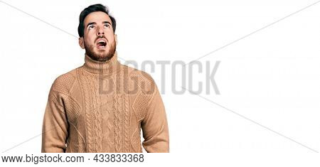 Young hispanic man wearing casual clothes angry and mad screaming frustrated and furious, shouting with anger. rage and aggressive concept.