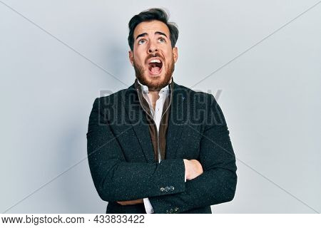 Handsome caucasian man with beard with arms crossed gesture angry and mad screaming frustrated and furious, shouting with anger looking up.