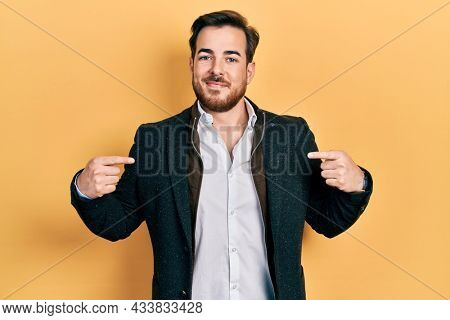Handsome caucasian man with beard wearing elegant business jacket looking confident with smile on face, pointing oneself with fingers proud and happy.