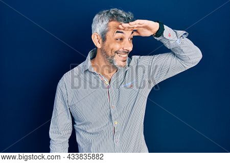 Handsome middle age man with grey hair wearing business shirt very happy and smiling looking far away with hand over head. searching concept.