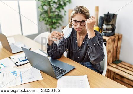 Young blonde woman working at the office wearing safety mask annoyed and frustrated shouting with anger, yelling crazy with anger and hand raised