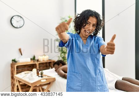 Young therapist woman at wellness spa center approving doing positive gesture with hand, thumbs up smiling and happy for success. winner gesture.
