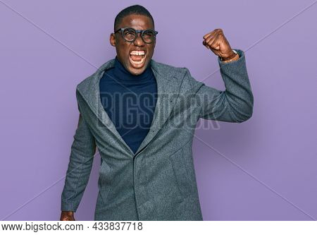 Young african american man wearing business clothes and glasses angry and mad raising fist frustrated and furious while shouting with anger. rage and aggressive concept.