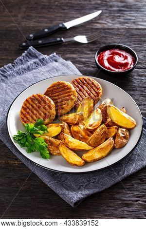 Grilled Fish Burgers With Baked Potato Wedges On A Plate