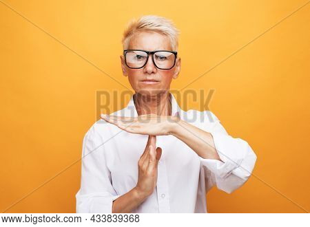 Gesture, prohibition and old people concept: Senior woman with short grey hair making time out sign