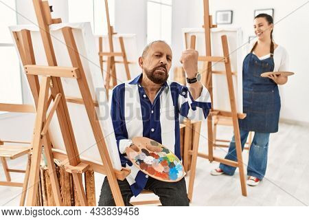 Senior artist man at art studio angry and mad raising fist frustrated and furious while shouting with anger. rage and aggressive concept.