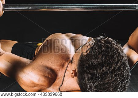 Selective Focus On The Naked Torso Of A Man Bench-pressing In A Gym