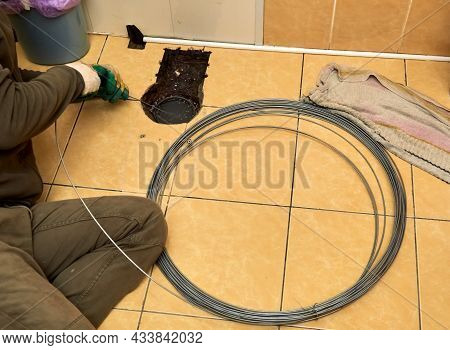 Sewer Cleaning. A Plumber Uses Sewer Snake To Clean Blockage Clog. Toilet Room Repair. Canalization