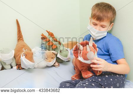 Child Plays Role-playing Games. Baby Bay And His Dinosaurs Toys Wearing Medical Mask And Sitting On